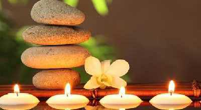 Image That Shows Four Massage Stones were Placed on the Table infront of the Four Candles.