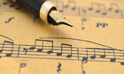 Image That Resembles An Ink Pen Placed on the Brown Musical paper.