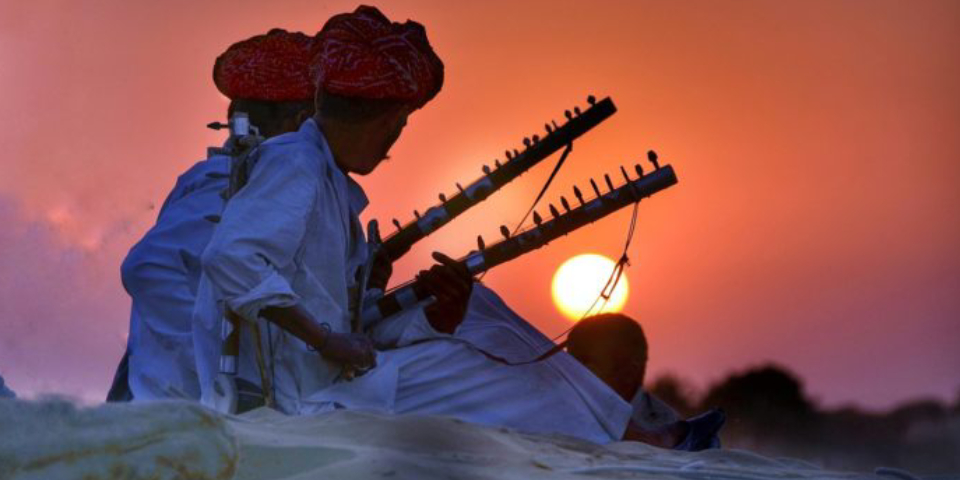 Two Folk Singers Playing Their Instruments In A Beautiful Sunset Background.