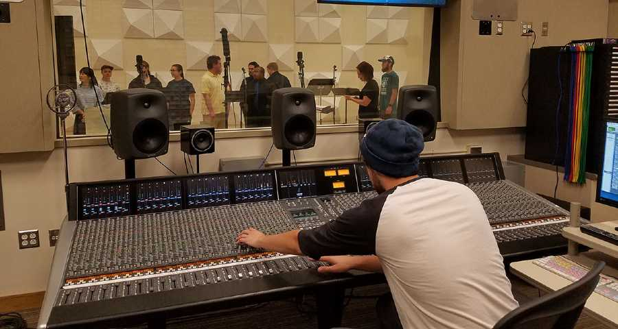 Professional music band recording song in boutique recording studio.